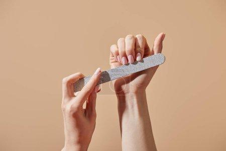 Photo pour Vue partielle d'une femme déposant des ongles avec un carton d'émeri isolé sur un beige - image libre de droit