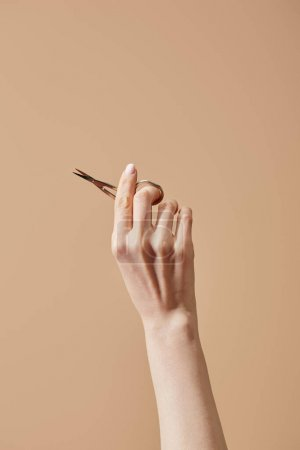 Photo pour Vue agrandie de la main de la femme avec ciseaux à ongles isolés sur du beige - image libre de droit