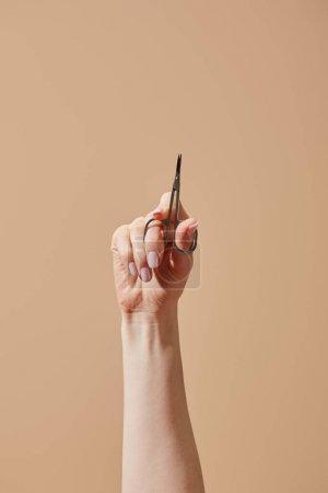 Photo pour Vue partielle de la main de la femme avec ciseaux à ongles isolés sur du beige - image libre de droit
