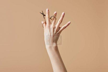 Photo pour Vue en croûte d'une femme tenant des ciseaux à ongles isolés sur du beige - image libre de droit
