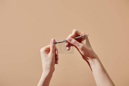 Photo for Cropped view of woman doing manicure using cuticle pusher isolated on beige - Royalty Free Image