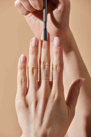 Photo for Partial view of woman doing manicure with cuticle pusher isolated on beige - Royalty Free Image
