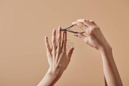 Photo pour Vue partielle de la femme faisant manucure avec une pince à cuticule isolée sur beige - image libre de droit