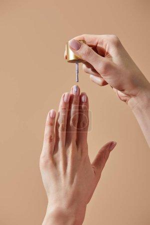 Photo pour Vue partielle d'une femme faisant de la manucure avec du vernis à ongles isolé sur beige - image libre de droit