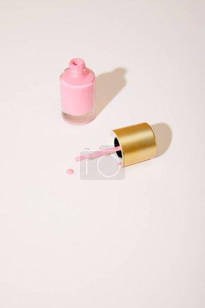 Photo pour Vue à grand angle de la bouteille ouverte de vernis à ongles rose sur fond blanc - image libre de droit