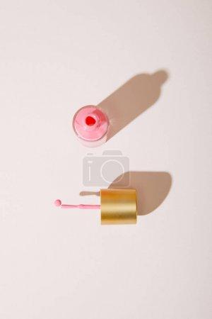 Photo pour Vue du haut d'une bouteille ouverte de vernis à ongles rose sur fond blanc - image libre de droit