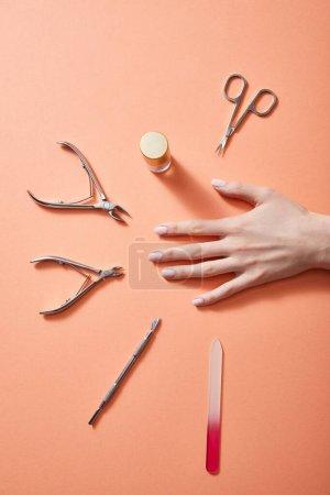 Photo pour Vue agrandie de la main de la femme avec bouteille de vernis à ongles et instruments de manucure sur corail - image libre de droit