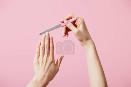 Photo pour Vue partielle d'une femme portant un ongle avec une lime à ongles isolée en rose - image libre de droit