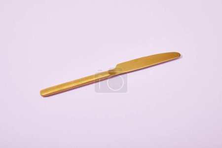 Foto de Cuchillo de oro brillante de metal sobre fondo violeta. - Imagen libre de derechos