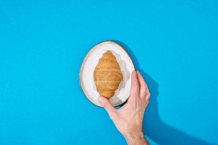 abgeschnittene Ansicht eines Mannes mit frischem Croissant auf Teller auf blauem Hintergrund