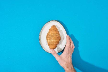vista recortada del hombre sosteniendo croissant fresco en el plato sobre fondo azul