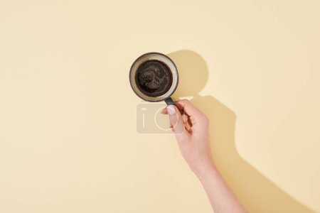 cropped view of woman holding cup of fresh coffee on beige background