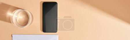 panoramic shot of smartphone, glass of water and envelope on beige background