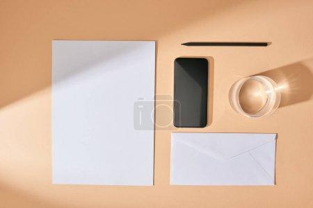 Photo pour Pose plate avec feuille de papier, smartphone, crayon, verre d'eau et enveloppe sur fond beige - image libre de droit