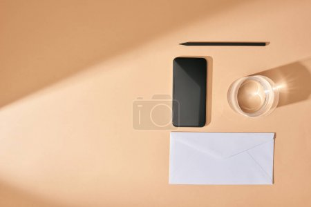 flat lay with smartphone, pencil, glass of water and envelope on beige background
