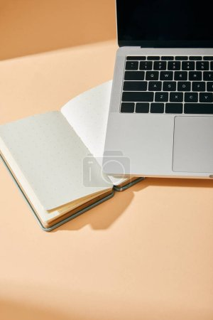 Photo for High angle view of opened blank notebook and laptop on beige background - Royalty Free Image