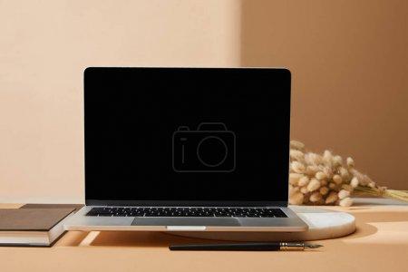 Photo pour Laptop avec écran vierge près des épillets de lagure, cahier et pinceau sur fond beige - image libre de droit