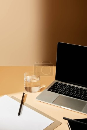 Photo for Laptop with blank screen near glass of water, pencil and paper on beige surface - Royalty Free Image