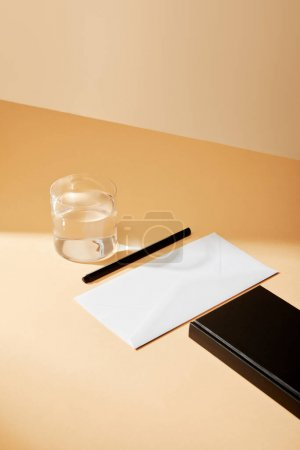 Photo for High angle view of envelope, pen, glass of water and black notebook on beige surface - Royalty Free Image
