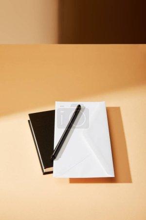 Photo pour Enveloppe, stylo et carnet noir sur surface beige - image libre de droit