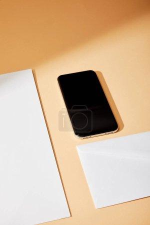 Photo pour Vue grand angle du smartphone près de l'enveloppe et feuille de papier sur fond beige - image libre de droit