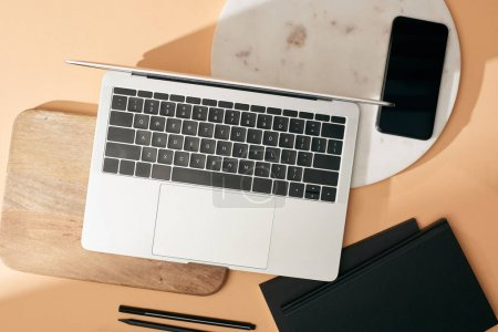 Photo for Top view of laptop on wooden and marble boards, smartphone, notebooks and pens on beige background - Royalty Free Image