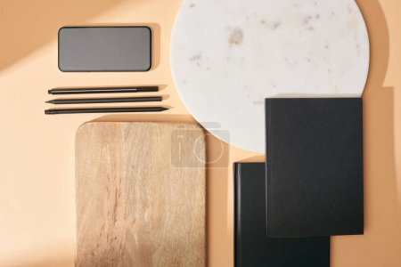 Photo for Top view of wooden and marble boards, smartphone, notebooks and pens on beige background - Royalty Free Image