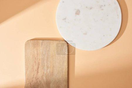 Foto de Vista superior de las tablas de madera y mármol sobre fondo beige. - Imagen libre de derechos