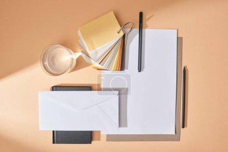 Photo pour Pose plate avec verre d'eau, échantillons de couleurs, feuilles de papier, stylos, enveloppe et carnet sur fond beige - image libre de droit