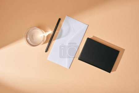 top view of envelope, pen, glass of water and black notebook on beige background
