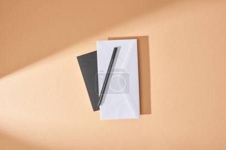 Photo pour Vue du dessus de l'enveloppe et du stylo sur carnet sur fond beige - image libre de droit