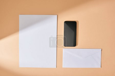 top view of sheet of paper, smartphone and envelope on beige background