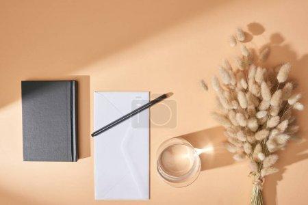 Photo pour Vue du haut du bloc-notes, enveloppe, stylo, verre d'eau et épillets lagurus sur fond beige - image libre de droit