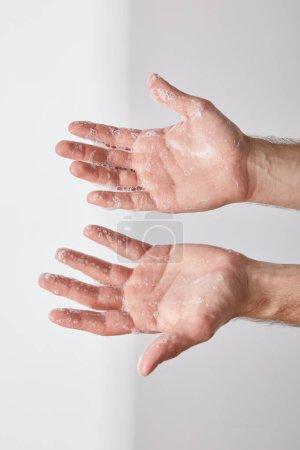 Teilansicht eines Mannes, der Hände mit Seifenschaum auf grauem Hintergrund zeigt