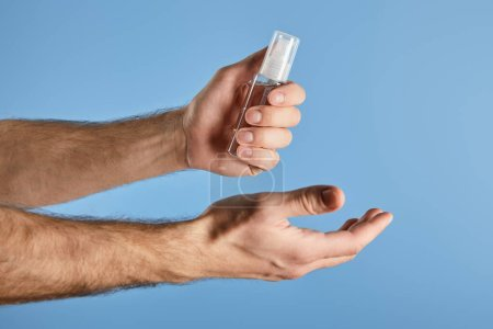 Photo pour Cropped view of man holding hand sanitizer in spray bottle isolated on blue - image libre de droit
