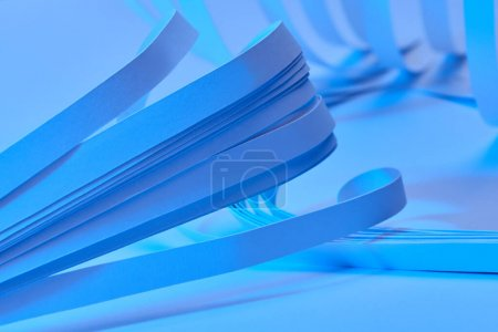 Photo for Close up view of curved paper stripes on neon blue background - Royalty Free Image