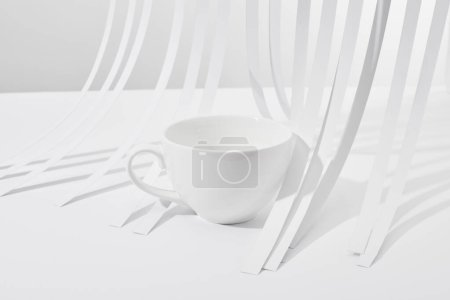 close up view of paper stripes and cup on white background