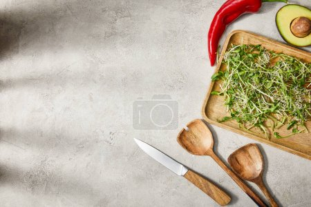 Photo for Top view of cutting board with microgreens, avocado half, chili pepper, spatulas and knife on grey background - Royalty Free Image