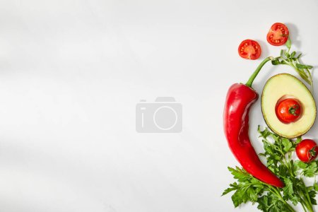 Top view of parsley, chili pepper, cherry tomatoes and avocado half on white background
