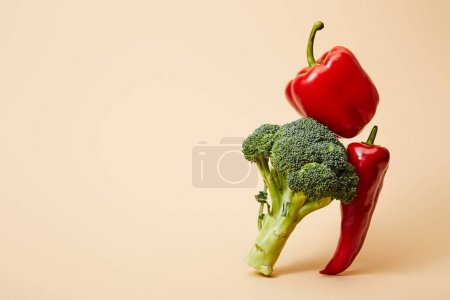 Photo for Ripe broccoli, bell and chili peppers on beige - Royalty Free Image