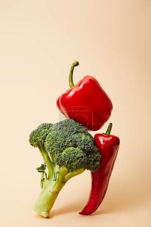 Photo for Fresh broccoli, bell and chili peppers on beige - Royalty Free Image