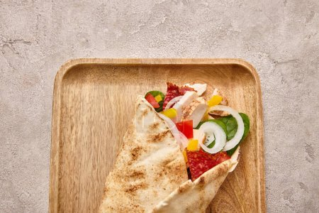 Photo for Top view of fresh burrito with chicken and vegetables on board on concrete grey background - Royalty Free Image