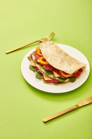 fresh sandwich with salami, pita, vegetables and cheese served on plate near golden fork and knife on green background