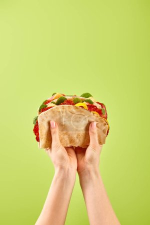 Foto de Partial view of woman holding fresh sandwich with salami, pita, vegetables and cheese isolated on green - Imagen libre de derechos