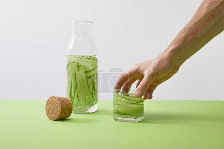 Photo pour Vue recadrée du verre à main mâle avec boisson faite de concombres tranchés et bouteille isolée sur gris - image libre de droit