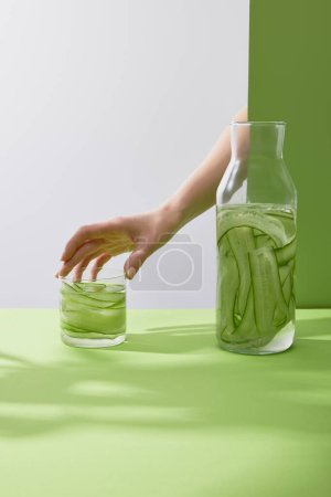 Photo for Cropped view of female hand touching glass with drink made of sliced cucumbers on grey and green background - Royalty Free Image