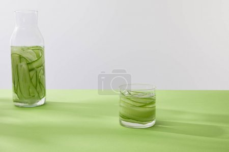 Photo for Bottle and glass with drink made of sliced cucumbers on green surface isolated on grey - Royalty Free Image