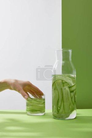 Photo pour Vue recadrée du verre à main féminin avec boisson fraîche faite de concombres tranchés et bouteille sur fond gris et vert - image libre de droit