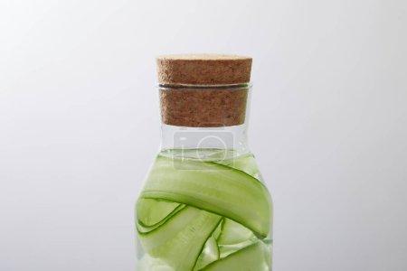 Vista de cerca de la botella de vidrio con corcho con bebida hecha de pepinos cortados en rodajas aislados en gris