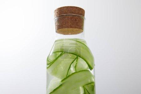 Nahaufnahme der Glasflasche mit Korken gefüllt mit Wasser und Gurkenscheiben auf grauem Hintergrund